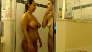 Two lustful lesbian friends kiss each other in the shower